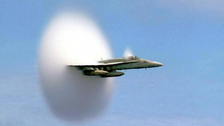 """Ein Kampfflugzeug durchbricht die Schallmauer. Auch wenn es toll aussieht: Das Weiße ist nicht etwa das Loch in der Schallmauer, sondern die """"Wolkenscheibe"""" aus kondensierten Wassertröpfchen an der Stoßwelle.Foto: US Navy/John Gay"""